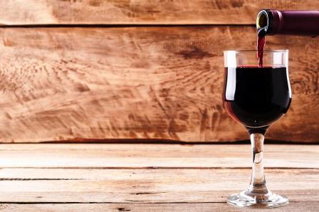 červené víno tečie z fľaše do pohára