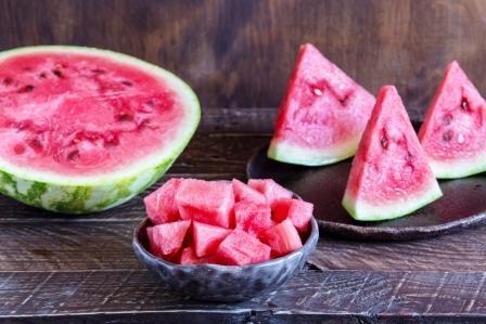 červený melón vodový porcovaný na polovicu ako trojuholník i kocky v miske