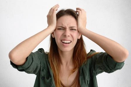 žena si drží hlavu rukami a je neštastná
