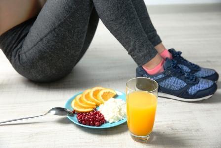Žena sedí na podlahe a vedľa seba má zdravé raňajky