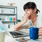 žena zíva pri počítaci, v ruka drží šálku