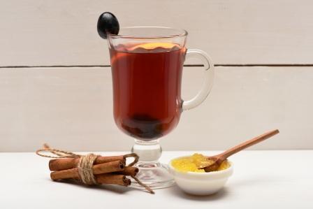 hromada škoricových tyčiniek vedľa šálky medu s drevenou lyžičkou zblízka