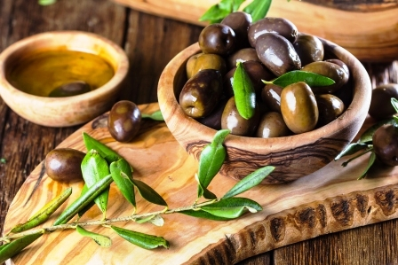Olivy a olivovy olej v olivovych drevenych miskach