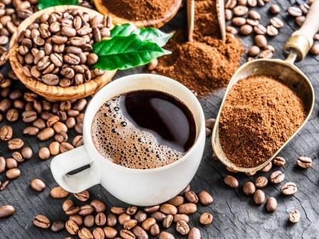 Prazene kavove zrna, mleta kava a salka kavy na drevenom stole