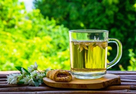 Sklenené šálky bylinného čaju jazmínového čaju a jazmínových kvetov