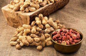 arašidy nelúpané i lúpané v miske na vrecovine a dreve