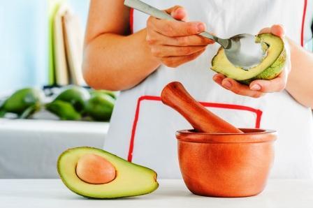 avokádo žena pripravuje tradičnú mexickú omáčku Guacamole z čerstvého avokáda