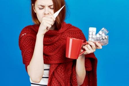 chorá žena drži v ruke teplomer a lieky