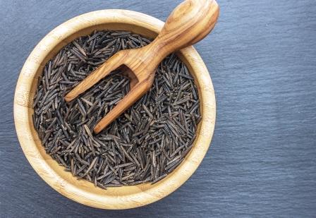 divoká ryža v miske s drevenou lyžičkou