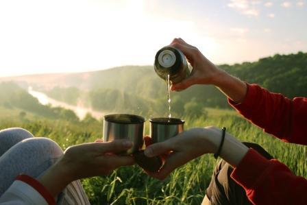 dvaja ľudia pijú bylinkový čaj s medom z termosky