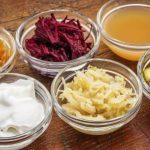 fermentované potraviny v miskách - jablčný ocot, uhorka, cvikľa, kapusta