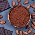 kakaovy prasok v miske s cokoládou a kakaovymi bobmi