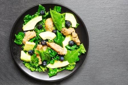 kurací šalát s avokádom, špenátom a čučoriedkami servírovaný na tanieri - super zdravé jedlo