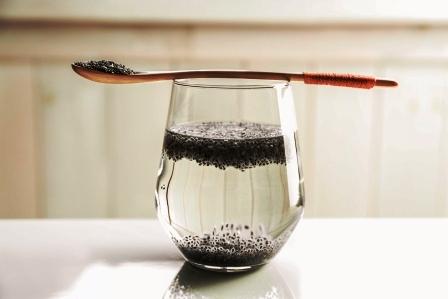 lyzica, pohar vody a chia semena na stole