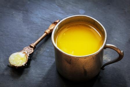 maslo ghee v hrnčeku a na drevenej lyičke