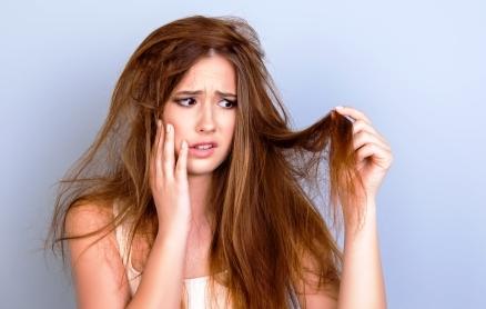 mladá žena si drží vlasy - má ich rozštiepené a nezdravé