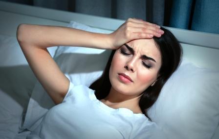 mladá žena trpí bolesťou hlavy, leží v posteli