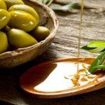 olivový olej na drevenej lyžičke, listy olivovníka a čerstvé olivy v miske