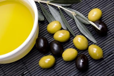 olivový olej v miske a zelené i čierne olivy na prútenej podložke