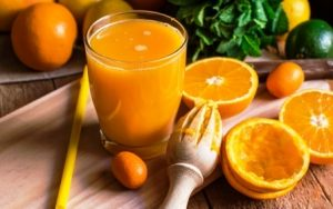 pomaranc rozkrojeny a odstavneny pomarancoby dzus v pohari