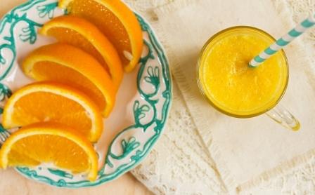 pomarancovy dzus v pohary a platky pomaranca na tanieriku