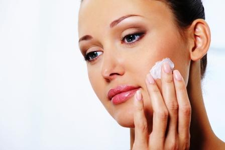 staranie o pleť mladá žena si na tvár natiera krém