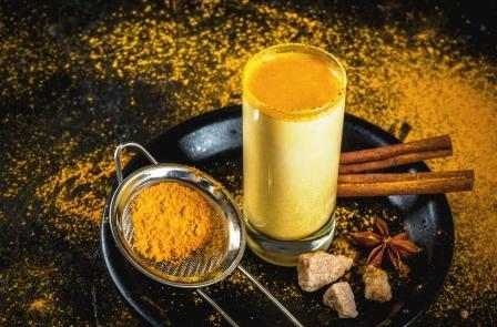 zlaté mlieko v pohári - kurkuma, rastlinné mlieko, škorica na čiernej tácke, v pozadí prášok z kurkumy