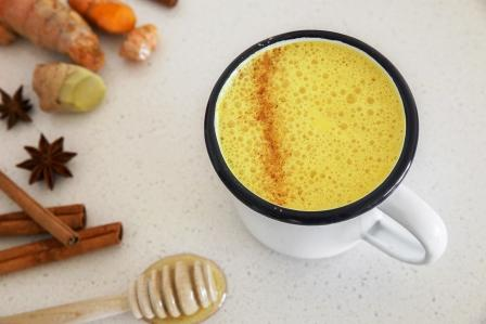 zlaté mlieko z kurkumy v hrnčeku ochutené škoricou, zázvorom a medom