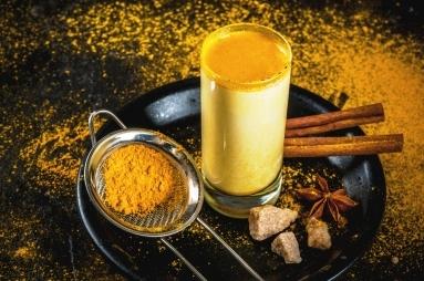 zlaté kurkumové mlieko v poháry a prášok z kurkumy a škorica